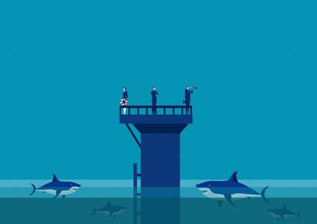 Equipe de negócios na parede no meio da equipe do mar cercada por tubarões.