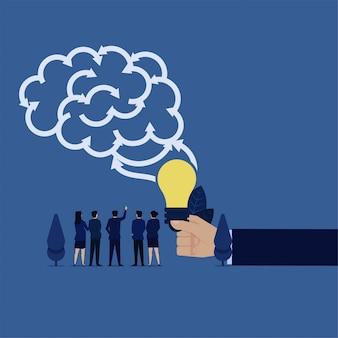 Equipe de negócios vê cérebro feito de seta para cada direção e mão segure a idéia.