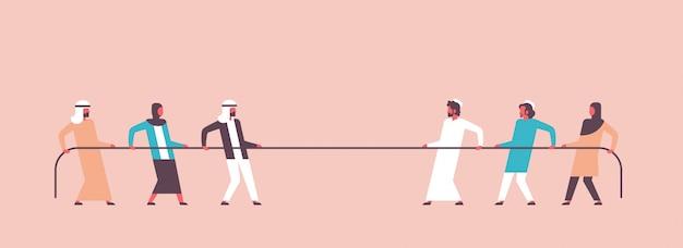 Equipe de pessoas árabes de cabo de guerra puxando extremidades opostas da corda