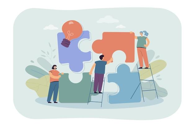 Equipe de pessoas minúsculas conectando elementos de quebra-cabeças gigantes