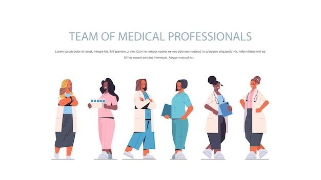 Equipe de profissionais da área médica mistura de mulheres médicas de raça uniformizada em pé juntos medicina conceito de saúde horizontal completo cópia espaço ilustração vetorial