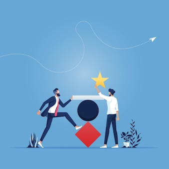 Equipe trabalhando em conjunto para organizar um objeto na forma de triângulo, círculo, retângulo e estrela para se tornar uma torre