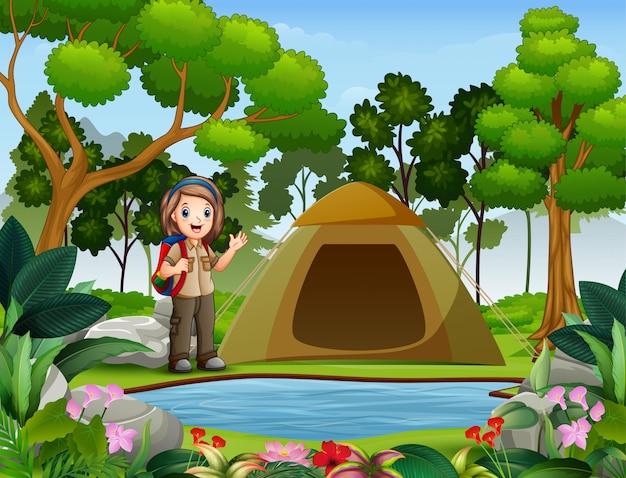 Escoteira no exterior com tenda e mochila