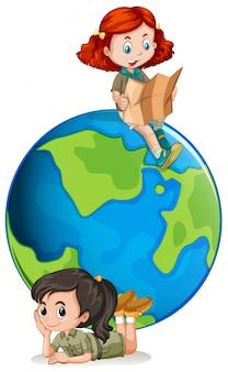 Escoteiras jovens na frente de um globo