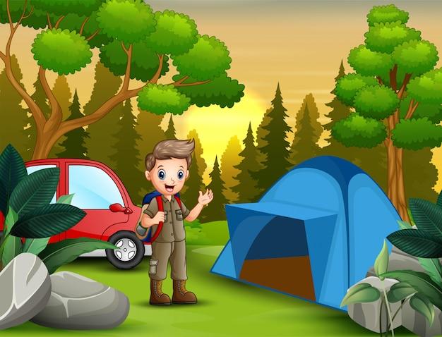 Escoteiro com mochila em pé perto da tenda