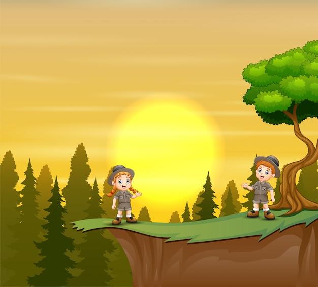 Escoteiro menino e menina em pé na montanha falésia do pôr do sol