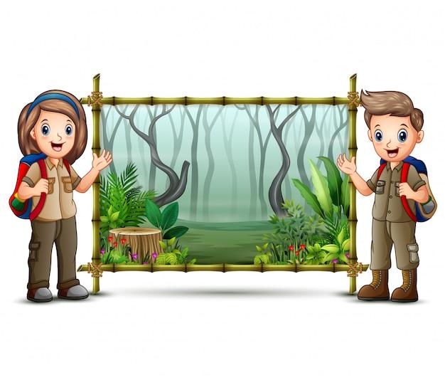 Escoteiro menino e menina perto da moldura de bambu verde
