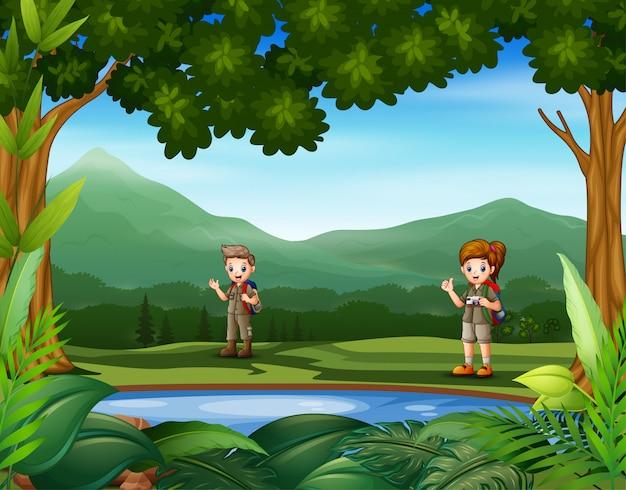 Escoteiros em pé ao redor do pequeno lago