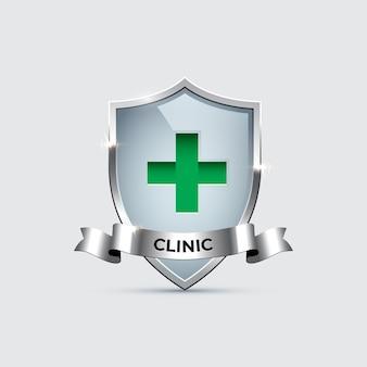 Escudo de vidro com moldura de prata com cruz sinal verde e fita de prata com palavra clínica.