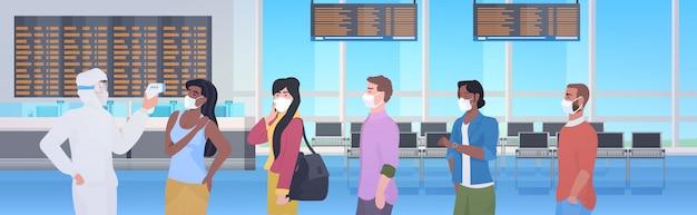 Especialista em traje de proteção, verificando a temperatura dos passageiros na pandemia de coronavírus do terminal do aeroporto