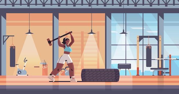 Esportista batendo no pneu com a menina hummer fazendo exercícios difíceis, treino de fitness, estilo de vida saudável, interior moderno ginásio
