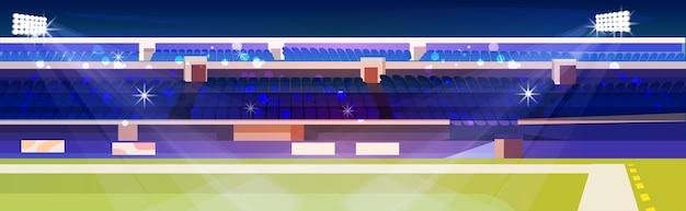 Estádio de futebol vazio com gramado verde e tribunas azuis horizontais