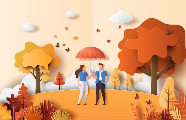 Estilo de arte papel de paisagem de outono com lindo casal apaixonado, segurando um guarda-chuva em um parque. Vetor Premium