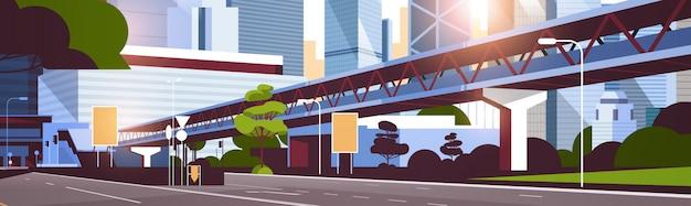Estrada estrada para o horizonte da cidade com arranha-céus modernos e metrô