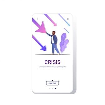 Estressado empresário americano africano parando econômico seta caindo crise financeira falência investimento risco conceito telefone tela móvel app comprimento total