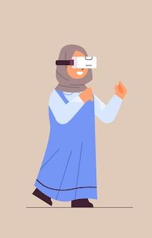 Estudante árabe usando fone de ouvido vr menina sorridente em óculos digitais explorando serviços interativos de realidade virtual ilustração vetorial de corpo inteiro vertical