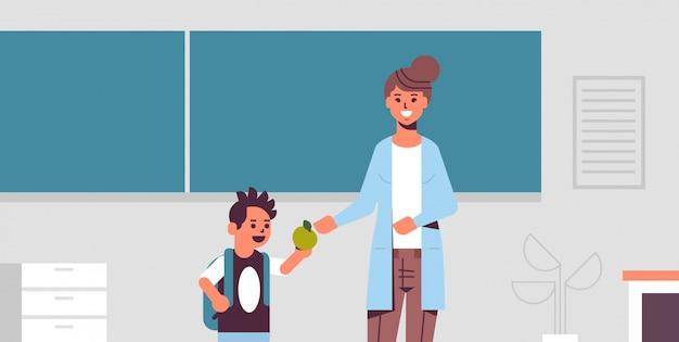 Estudante dando maçã ao professor em frente a placa de giz verde conceito de educação conceito moderno sala de aula interior retrato horizontal