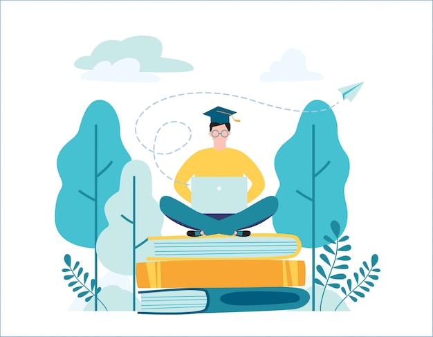 Estudante graduado do sexo masculino sentado em livros com laptop rodeado por vegetação