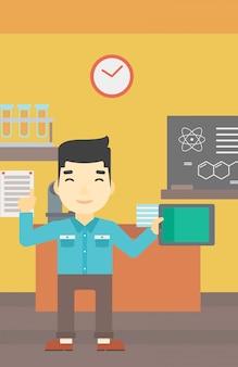 Estudante masculino que usa o tablet pc na sala de aula.