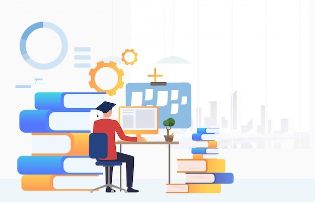 Estudante no chapéu de formatura, usando o computador na mesa