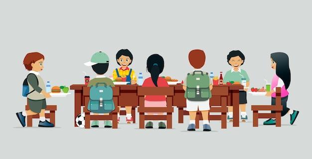 Estudantes masculinos e femininos estão sentados à mesa com o almoço
