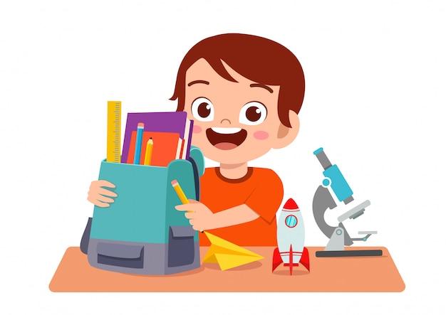 Estudo de menino feliz criança fofa na mesa bonitinha