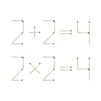 Expressões matemáticas dois mais dois iguais quatro e duas vezes dois iguais quatro feitos de fósforos marrons close-up vista superior em fundo branco