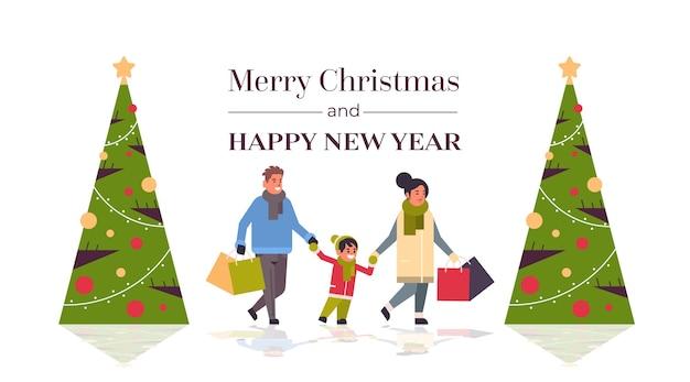 Família caminhando com sacos de papel coloridos feliz natal feliz ano novo conceito de compras de inverno pais com criança segurando compras saudação