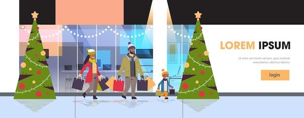 Família caminhando com sacos de papel coloridos feliz natal feliz ano novo conceito de compras pais com criança segurando banner exterior de shopping moderno