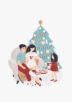 Família com uma criança bebe cacau na árvore de natal