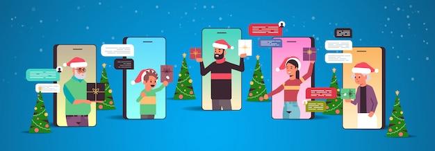 Família de várias gerações em chapéus de papai noel usando o conceito de comunicação de aplicativo de bate-papo de rede social de bate-papo