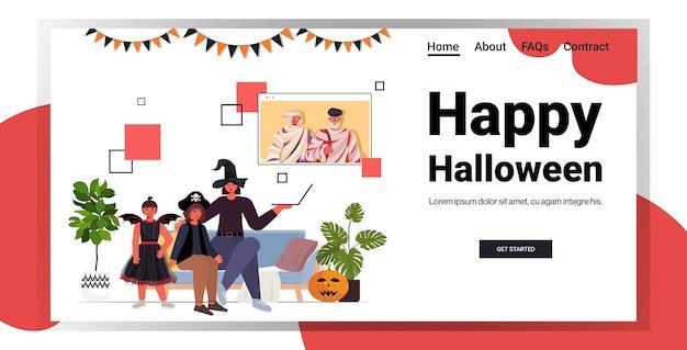Família feliz do conceito de celebração do feriado de halloween em fantasias, discutindo com os avós durante a videochamada