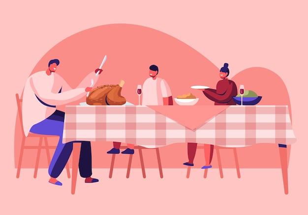 Família feliz, pai e filhos sentados à mesa com bebidas e comidas festivas