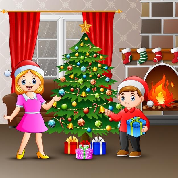 Família feliz que decora uma árvore de natal com bolas
