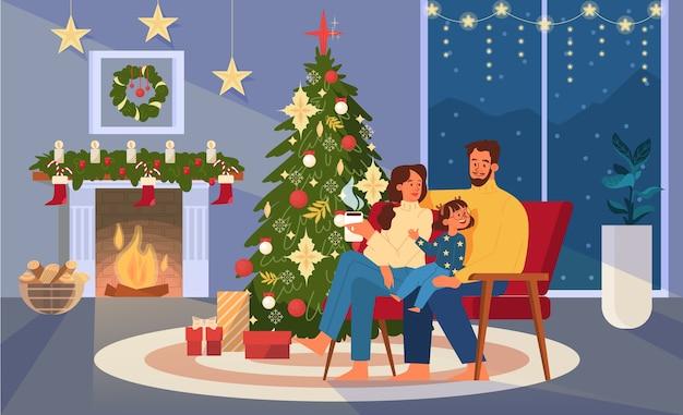 Família feliz sentada ao lado da árvore de natal, segurando uma xícara de chocolate.