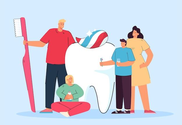 Família minúscula feliz e dente branco gigante