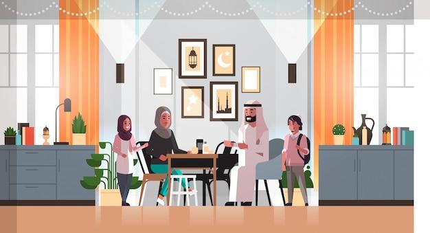 Família muçulmana comemorando ramadan kareem mês sagrado sala interior árabes pais e filhos em roupas tradicionais, passar tempo juntos apartamento horizontal comprimento total