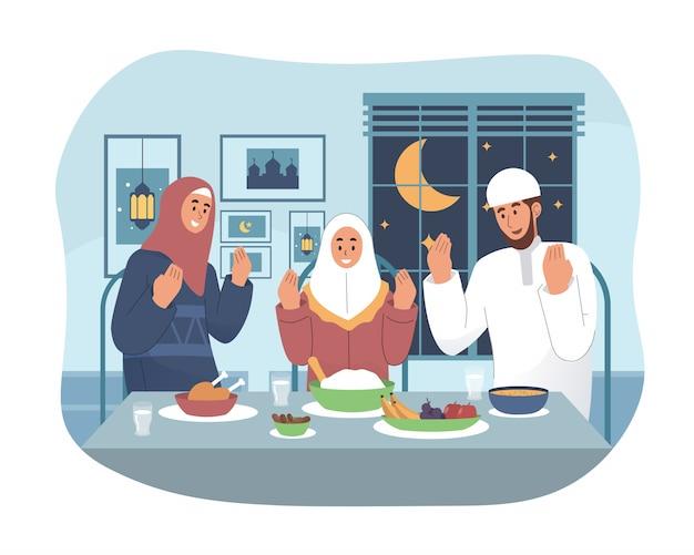 Família muçulmana rezando antes de ter iftar
