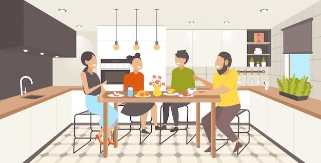 Família sentada à mesa de jantar pais e filhos tomando café da manhã cozinha moderna interior comprimento total horizontal