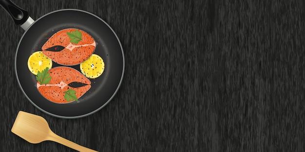 Fatia de peixe vermelho com os limões na frigideira no fundo preto de madeira.