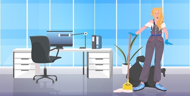 Faxineira profissional feminina faxineira com equipamento de limpeza esfregando chão escritório moderno interior cópia espaço horizontal