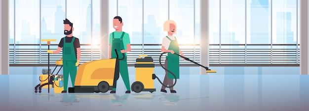 Faxineiros equipe de limpeza serviço de limpeza de uniforme trabalhando em conjunto com equipamento profissional salão moderno interior janelas panorâmicas paisagem urbana