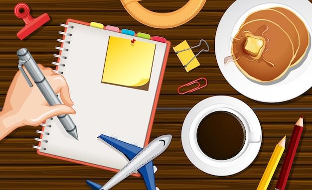 Feche a mão, escrevendo no notebook com modelo de avião e xícara de café no fundo da mesa