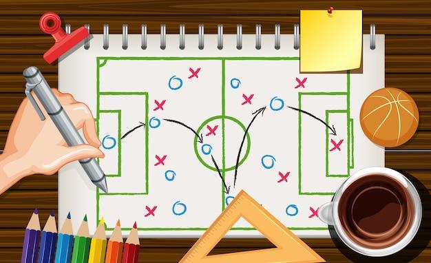 Feche a mão escrevendo o plano de basquete no caderno