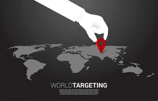 Feche acima da mão do marcador do pino do lugar do lugar do homem de negócios na frente do mapa do mundo. conceito de ai aprendendo máquina e sistema de navegação.