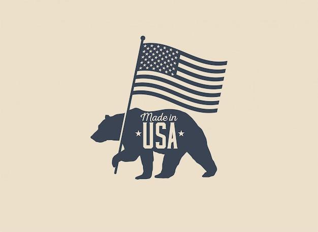 Feita nos eua etiqueta distintivo ou design de logotipo com urso segurando a silhueta da bandeira americana isolada na luz de fundo. ilustração com estilo vintage.
