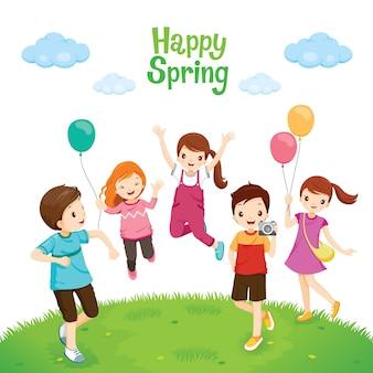 Felicidade, crianças relaxando, pulando no gramado, feliz primavera