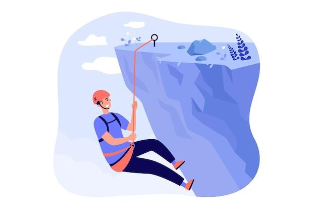 Feliz alpinista escalando montanhas rochosas, segurando corda e pendurado em um penhasco.