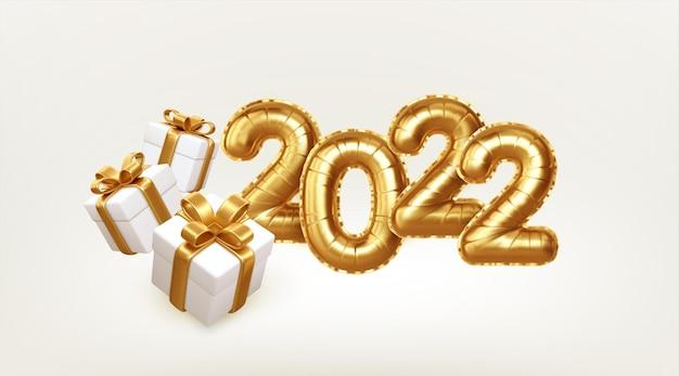 Feliz ano novo 2022 balões de folha de ouro metálico e caixas de presente em fundo branco. os balões de hélio dourado chegam a 2.022 no ano novo. ilustração vetorial eps10
