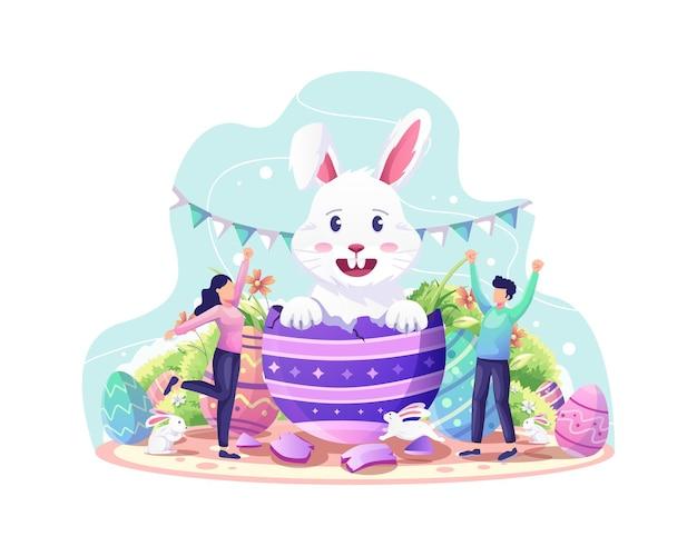 Feliz celebração do dia de páscoa com um casal dando as boas-vindas ao coelho fofo saindo do ovo da páscoa